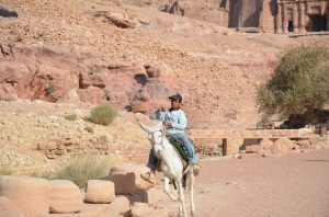 A boy riding His donkey in Petra